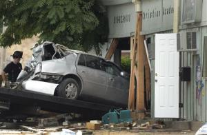 A car is pulled from a day care center after it crashed into the building in Kansas City today.