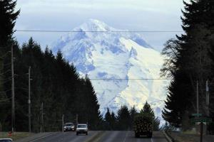 Mount Hood looms over Highway 26 near Sandy, Ore., in this December 14, 2011, file photo. The search is resuming this morning for a snowboarder buried when an ice tunnel collapsed.