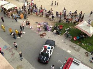 Pedestrians gather as police and fire officials respond after a car drove through a packed afternoon crowd along the Venice Beach boardwalk in Los Angeles, Saturday, Aug. 3, 2013.