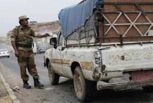 A Yemeni soldier stops a car at a checkpoint in a street leading to the US embassy in Sanaa, Yemen, Sunday, Aug. 4, 2013.