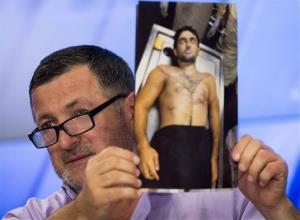 Abdul-Baki Todashev holds a photo  of his dead son Ibragim Todashev.