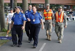 Transportation Security Administration employees walk with National Guard soldiers on the periphery during the Boston Pops Fourth of July Concert at the Hatch Shell in Boston, Thursday, July 4, 2013.