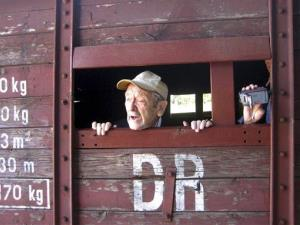 Holocaust survivor Adolek Kohn looks out the window of a train freight car that used to transport people to the Auschwitz death camp in Poland, in this undated image.