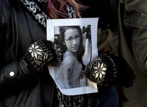 In this file photo, a woman holds a photo of Rehtaeh Parsons at a vigil in Halifax, Nova Scotia, Canada.