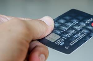 A man holding his credit card.