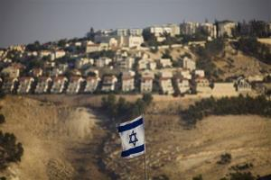 In this Monday, Sept. 7, 2009 file photo, an Israeli flag is seen in front of the West Bank Jewish settlement of Maaleh Adumim on the outskirts of Jerusalem.