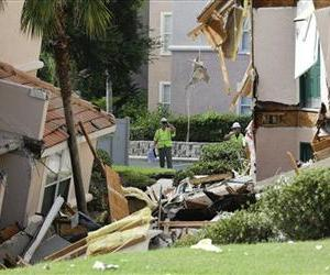 Inspectors look over damage to buildings caused by a sinkhole 40 to 50 in diameter at the Summer Bay Resort, Monday, Aug. 12, 2013, in Clermont, Fla.