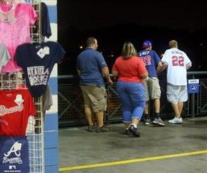 Baseball fans look over  a railing at Turner Field near the scene where a man fell 65 feet from the upper deck Monday, Aug. 12, 2013.