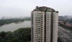 This Aug. 12, 2013 photo released by China's Xinhua News Agency shows a residential building with a rocky style villa on its roof, in Haidian District of Beijing, China.