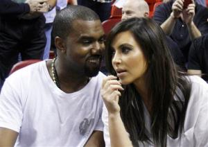 This Dec. 6, 2012 file photo shows singer Kanye West, left, talks to his girlfriend Kim Kardashian before an NBA basketball game between the Miami Heat and the New York Knicks in Miami.