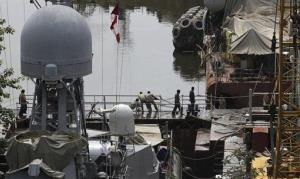 Indian navy sailors work at a naval dockyard where a submarine caught fire and sank after an explosion early Wednesday in Mumbai, India, Aug. 14, 2013.