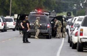 Louisiana state, federal, and local law enforcement gather along La. Highway 128 outside a Tensas State Bank branch during a hostage situation in St. Joseph, La., Tuesday, Aug. 13, 2013.