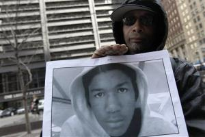 Steven Bishop, of Raleigh, N.C. holds a photo of Trayvon Martin during an Occupy Wall Street march, Saturday, March 24, 2012 in New York.