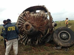 National Transportation Safety Board (NTSB) Investigators examine debris of a UPS A300 cargo plane after it crashed on approach at Birmingham-Shuttlesworth International Airport, Wednesday, Aug. 14, 2013, in Birmingham, Ala. The two pilots aboard the airplane were killed.