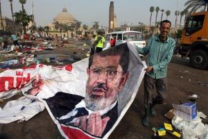An Egyptian pulls a banner of Egypt's ousted President Mohammed Morsi near debris left at a protest camp in Nahda Square in Cairo Thursday.