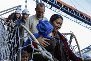 Hannah Gastonguay, holding her baby Rahab, is followed by her husband Sean and the couple's 3-year-old daughter Ardith, as they disembark in the port city of San Antonio, Chile, Friday, Aug. 9, 2013.