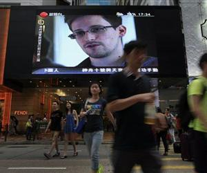 This June 23, 2013 file photo shows a TV screen with a news report on Edward Snowden at a shopping mall in Hong Kong.