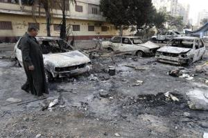 An Egyptian man walks through debris from what is left of burned vehicles outside the Rabaah al-Adawiya mosque in Cairo.