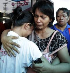 A survivor, left, of the ill-fated passenger ferry MV Thomas Aquinas, is comforted by a relative.
