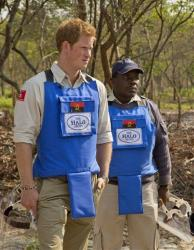 Britain's Prince Harry, left, is given a tour around the current mine clearance site by HALO's provincial manager Tony Jose Antonio in Angola.