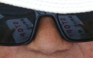 Signs are reflected in a North Korean defector's sunglasses during a rally near the Chinese Embassy in Seoul.