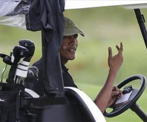 President Obama gestures from his golf cart off while golfing at Vineyard Golf Club in Edgartown, Mass., on the island of Martha's Vineyard, Aug. 18, 2013.