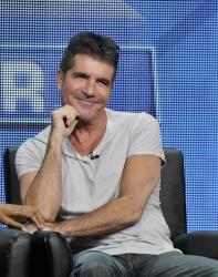 Simon Cowell smiles from the stage during a panel discussion on The X Factor at the FOX 2013 Summer TCA press tour at the Beverly Hilton Hotel on Thursday, Aug. 1, 2013, in Beverly Hills, Calif.