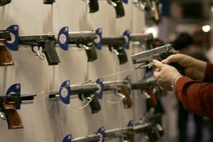 In this file photo, a woman points a handgun with a laser sight on a wall display during a National Rifle Association convention.