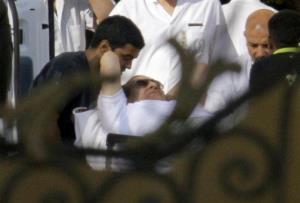 Egyptian medics escort Hosni Mubarak into an ambulance after he was flown to a military hospital.