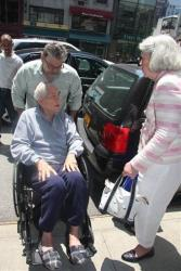 In this June 21, 2013 file photo, an unidentified man pushes Anthony Marshall in a wheelchair while his wife, Charlene Marshall, speaks to him outside his residence in New York.