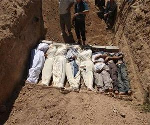 Several bodies are buried in a suburb of Damascus, Syria during a funeral on Wednesday, Aug. 21, 2013.