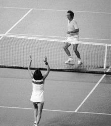 In this 1973 file photo. Billie Jean King raises her arms after defeating Bobby Riggs, rear, getting ready to jump over the net, in the Battle of the Sexes.