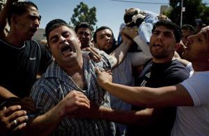 Palestinian mourners react while carrying the body of slain Palestinian Jihad Aslan, 19 toward the morgue of the main hospital at the West Bank town of Ramallah, Monday, Aug. 26, 2013.