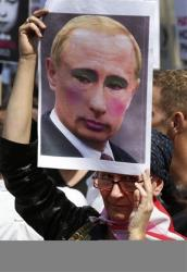An activist holds a placard depicting Putin in make-up at a protest in London earlier this month.