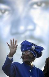 A file photo of Christine King Farris standing in front of an image of her brother, MLK.