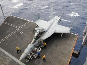 US Navy crew members work on a fighter jet aboard the USS Nimitz aircraft carrier.