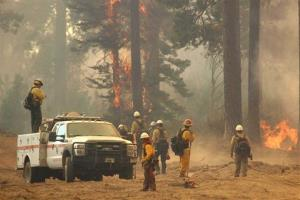 In this Friday, Aug. 30, 2013 photo, a fire crew stands watch along a fire break near a burn operation on the southern flank of the Rim Fire near Yosemite National Park in California.