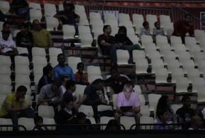 A fan looks at his laptop as he waits for play to resume at a FIBA World Cup qualifying basketball game, during a power outage, in Caracas,Venezuela, Tuesday, Sept. 3, 2013.