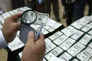 A police officer inspects an alleged counterfeit 100 U.S. dollar note during a press conference to show the currency to the press in Lima, Peru, Friday, Aug. 17, 2012.