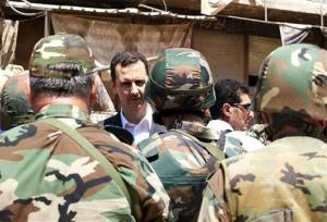 This file photo posted on the official Facebook page of the Syrian presidency appears to show Syrian President Bashar Assad talking with soldiers in Darya, Syria.