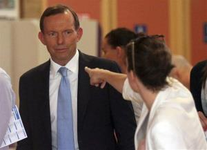 A woman points at Australia's opposition leader Tony Abbott while he waits to cast his vote at a Sydney polling station.