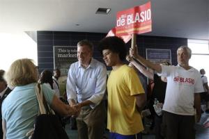 Democratic mayoral hopeful Bill de Blasio, center, and his son Dante greet commuters at the Staten Island ferry terminal.