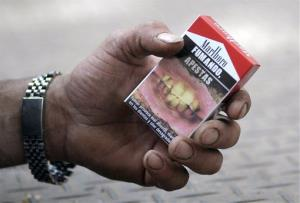A man shows his cigarette package covered by a warning that reads in Spanish Smoking, you stink, top, and Smoking causes bad breath in Montevideo, Uruguay.