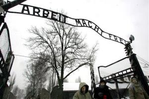 Visitors walk under the notorious Arbeit Macht Frei sign at the entrance gate of the Auschwitz Nazi concentration camp in Oswiecim, southern Poland.