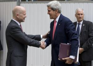 Britain Foreign Secretary William Hague, left, greets US Secretary of State John Kerry outside the Foreign Office in London today.
