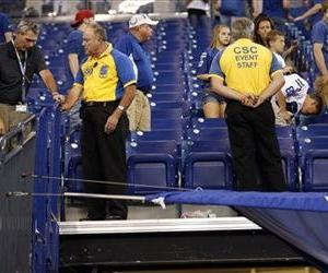 Stadium personnel look over the area where two men fell from the stands after a railing gave way as the Oakland Raiders were leaving the field following a game in Indianapolis, Sunday.