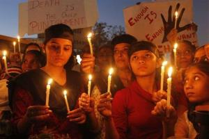 Indian women hold candles to condemn the brutal gang-rape of a woman on a bus in New Delhi last year.