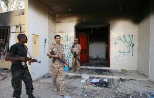 Libyan military guards check one of the US Consulate's burnt-out buildings after last year's attack.