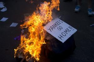A sing is burns during a march against US intervention in Syria in Buenos Aires, Argentina.