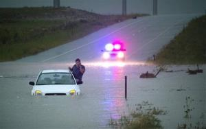 During a previous storm, a stranded motorist uses his cell phone as he waits for help Thursday night, August 22, 2013, in Colorado Springs, Colo.